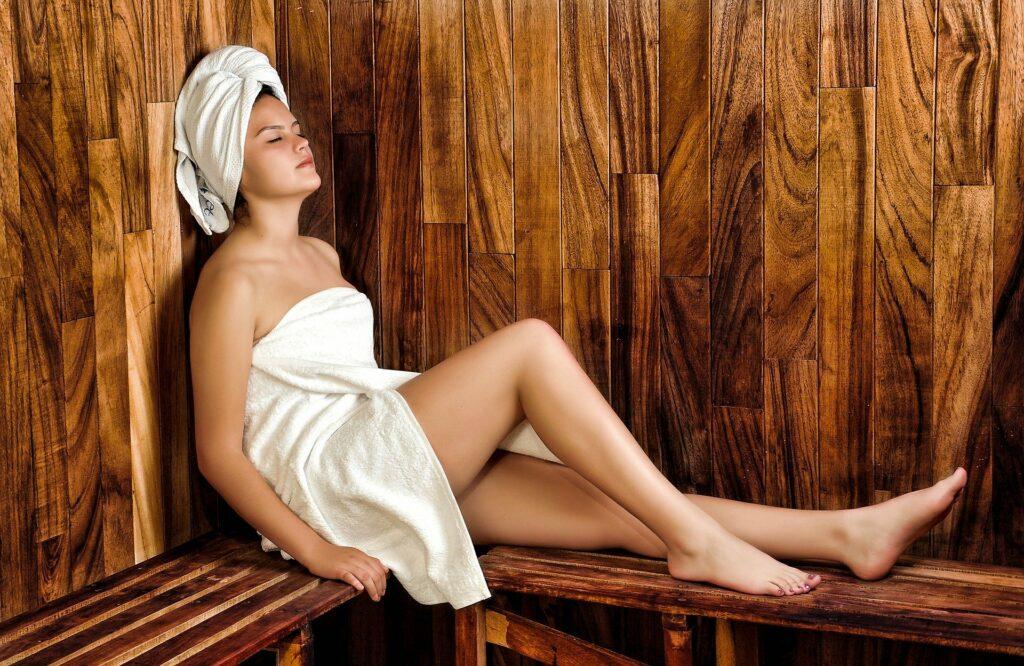 frau in der sauna mit handtuch erkältet